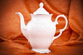Teapot isolated on orange fabric background — Stockfoto