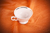 Small color coffee cup on orange fabric background — Stock Photo