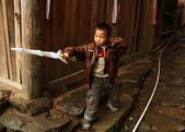 Chinese five year old boy playing with a plastic sword in the vi — Stock Photo