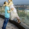 Happy couple walking on the roof of a high building, with views — Stock Photo