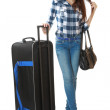 Slim girl in jeans and a plaid shirt, standing next to a big, black travel bag on wheels. The girl pulls hair. One person, teenager, female, vertical image, isolated on white background. — Stock Photo