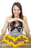 Yellow flowers dandelions in form of Heart. One teenage girl 16 years old, caucasian appearance, laid out on the table the heart of dandelion flowers. One person, female teenager, vertical, isolated. — Stock Photo