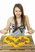 Girl shows heart of wildflowers. Heart of yellow dandelions. To lay out heart from flowers. Girl gathered on table image of heart of yellow dandelion flowers. Teen girl amounted heart of wildflowers. — Stock Photo