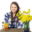 Foto Stock: Girl teenager, caucasiappearance, brunette, wearing plaid shirt, holding glass of drink. On table is blue vase, with bouquet of yellow wildflowers, dandelions. One teen girl, caucasian