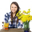 Стоковое фото: Girl teenager, caucasiappearance, brunette, wearing plaid shirt, holding glass of drink. On table is blue vase, with bouquet of yellow wildflowers, dandelions. One teen girl, caucasian