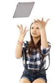 The girl throws in the air tablet PC . Teenage girl in a plaid shirt and short denim shorts, tosses a PC tablet to the top. Girl catches flying in air Tablet PC. Girl, throws up in the air PC tablet — Stock Photo