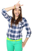 Teenage girl shows tongue and makes hand horns. Mint-colored pants and a plaid shirt. — Stock Photo