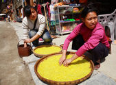 Dong ethnic women treated with rice on a street Zhaoxing Dong Village. Yellow rice is found in large wicker baskets. Zhaoxing Town, Liping County, Guizhou, China. — Stock Photo