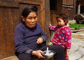 Grand-mère nourrit son petit-fils sur la rue près de la maison. — Photo