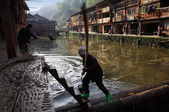 River in village Zhaohing GUIZHOU CHINA: Dong ethnic woman removes debris from surface of river village, man in river washes cloth to wash embankment of river village Zhaoxing Dong Village, April 2010 — Stock Photo