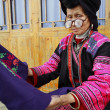 Stock Photo: Old womwith big glasses, red Yao nationality, ethnic minorities in China, holding blue cloth with patterns embroidered by hand, 4 April 2010. Xiaozhai Yao ethnic minority village, near Longsheng