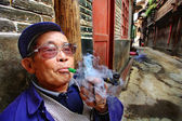 Chinese peasant smokes a tube before of his house. Age of Chinese man smoked a pipe and releases tobacco smoke. April 9, 2010. Zhaoxing Dong ethnic minority villages, Liping County. Guizhou, China. — Foto de Stock