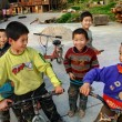 Chinese boys riding bikes on the Dong ethnic village peoples. — Stock Photo