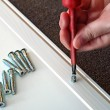 Stock Photo: Hand with Phillips screwdriver and screws, furniture assembled.