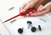 Assembling furniture, hand with screwdriver, adjustable plastic legs with screw. — Stock Photo