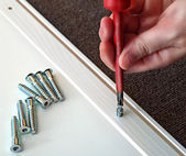 Hand with Phillips screwdriver and screws, furniture assembled. — Stock Photo