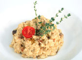 Restaurant dish, risotto with porcini mushrooms, decorated with rosemary. — Stock Photo