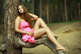 Girl in pink dress relaxing on forest glade, among pines. — Stock Photo