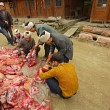 Stock Photo: Farmers cut up and sort asipork in chinese countryside.
