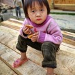 Asian child girl 4 years old, holding cookie, in countryside. — Stock Photo