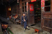 Asian trader in green sneakers, sits near a village shop. — Stock Photo