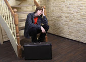 Teenage boy 14 years, sitting on wooden stairs near suitcase. — Stock Photo