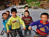 Funny Asian children from rural areas of China, ride bikes. — Stock Photo
