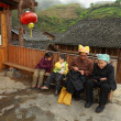 Stock Photo: Rural China, Asian grandmother with grandchildren, sit on bench.