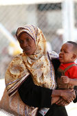 African Muslim women, large color scarf, holding baby her arms. — Stock Photo