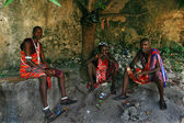Three young Africans, Masai clothing, rest in the shade. — Stock Photo
