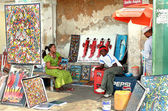 African souvenirs, Art shop outdoors, bright paintings sell, dark-skinned sellers. — Stock Photo