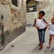 Tanzania, Zanzibar, Stone Town, two dark-skinned girls playing in street. — Stock Photo
