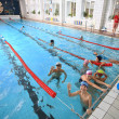 Stock Photo: Schoolchildren swim in covered sports public swimming pool.