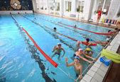 Schoolchildren swim in the covered sports public swimming pool. — Stock Photo