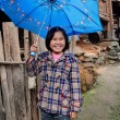 Rural Asian girl, about 8 years , hiding blue umbrella and laugh — Stock Photo