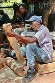 Art workshop outdoors woodcarver carves Maasai figurines. — Zdjęcie stockowe