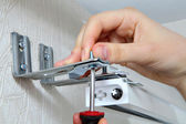 Vertical blinds mounting brackets, hand with a screw close up — Stock Photo