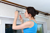 Girl hangs vertical blinds, tighten with a screwdriver, screw br — Stock Photo