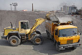 Yellow  excavator loads gravel into orange dumper truck tipper. — Stock Photo