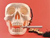 Human skull, cross, cigarette. — Stock Photo