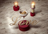 Love sign with candels on wooden background — Stock Photo