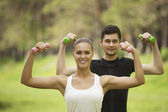 Cheerful couple with dumbbells on workout — Stock Photo
