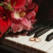 图库照片: Wedding rings on piano