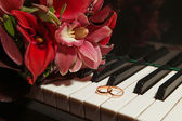 Wedding rings on the piano — Stock Photo