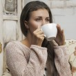 Girl drinking from a cup — Stockfoto