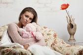 Sad girl hugging a teddy bear looks into the camera — Stock Photo