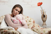 Sad girl hugging a teddy bear looks into the camera — Stock Photo