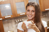 Girl holding a mug and smiling — Stockfoto