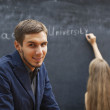 A couple of students at the blackboard with the words — Stock Photo