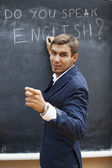 Young teacher writing on a blackboard with chalk — Stock Photo
